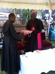 Bishop Kakooza Receiving a gift from Director Fr Kabanda